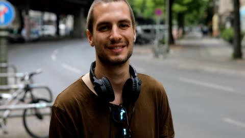 glücklicher mann mit kopfhörer und sonnenbrille in stadt - junge männer stock-videos und b-roll-filmmaterial