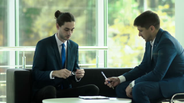 Happy man with keys makes a successful deal with manager in the office video