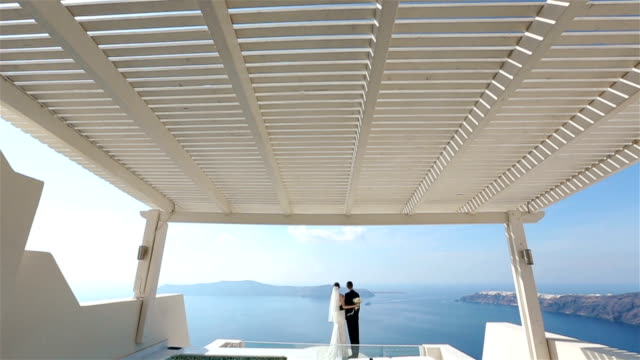 felice sposato coppia abbracciare sulla terrazza con mare sullo sfondo, santorini primo piano - isole egee video stock e b–roll