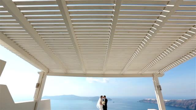 felice sposato coppia baciarsi sulla terrazza con mare sullo sfondo, santorini primo piano - isole egee video stock e b–roll