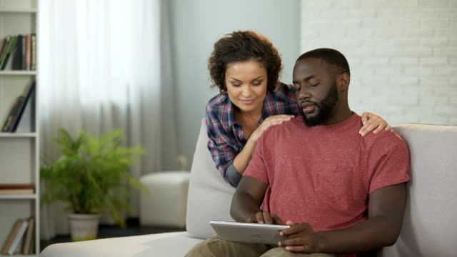 felice coppia sposata che pianifica un viaggio all'estero, scegliendo hotel e compagnie aeree online - fare una prenotazione video stock e b–roll