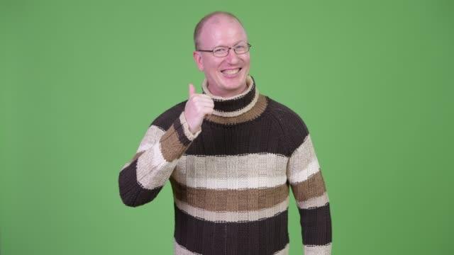 Homem calvo maduro feliz que dá os polegares acima prontos para o inverno - vídeo