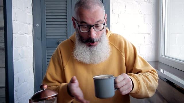幸せな成熟したひげを生やした男は、カップにあまりにも多くのコーヒーを注ぎ、カメラに飲み物を差し出します。ぼやけたキッチンの背景。 - あごヒゲ点の映像素材/bロール