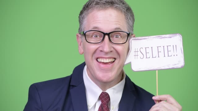 Happy mature businessman with eyeglasses holding selfie paper sign Studio shot of mature businessman with gray hair wearing eyeglasses against chroma key with green background prop stock videos & royalty-free footage