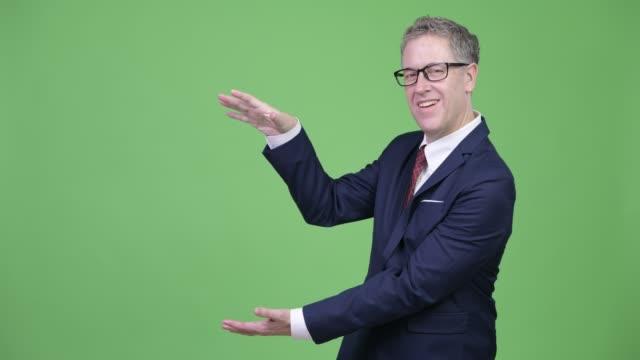 Homem de negócios maduro feliz com os eyeglasses que agarram dedos e que mostram algo - vídeo
