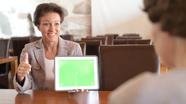 Happy Mature Businesswoman Showing Digital Tablet While Talking With Senior Woman
