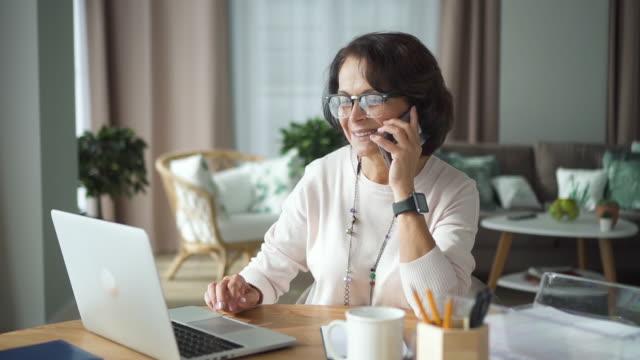 felice donna d'affari matura che parla telefono lavorando a tavola con laptop in ufficio - donne mature video stock e b–roll