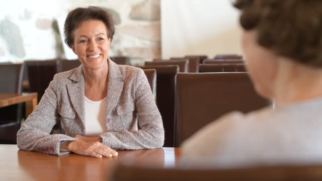 Happy Mature Businesswoman Talking With Senior Woman At The Coffee Shop