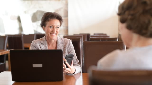 Happy Mature Businesswoman Using Technology While Talking With Senior Woman