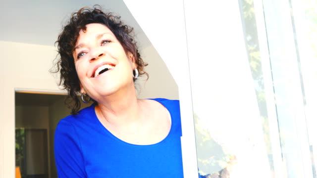 stockvideo's en b-roll-footage met gelukkig volwassen kaukasische vrouw zoekt uit een raam 4 k - photography curtains