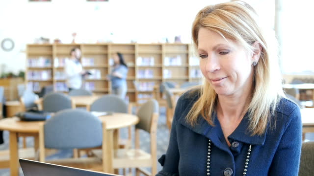 Happy mature Caucasian woman using laptop to video chat or study in college library video