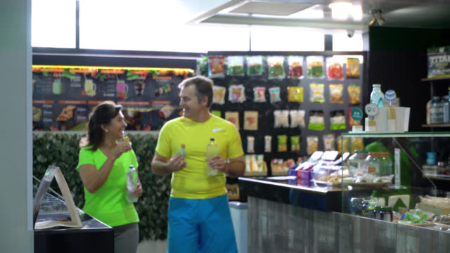 Happy mature couple at the food store gym enjoying a granola bar while talking and walking away Happy mature couple at the food store gym enjoying a granola bar while talking and walking away smiling sportsperson stock videos & royalty-free footage