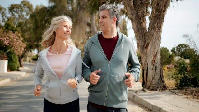 happy mature couple jogging together on sunny day in spring - capelli grigi video stock e b–roll