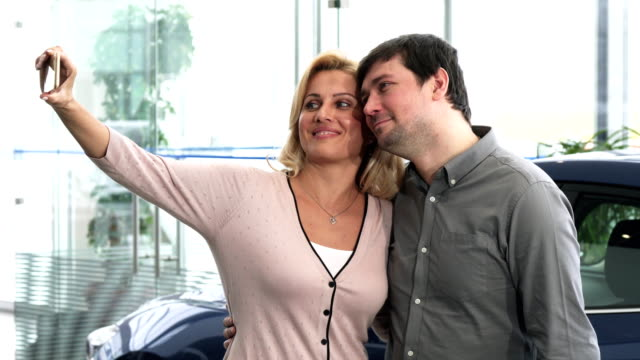 Happy mature couple taking sefies at the car dealership shopping for new auto video