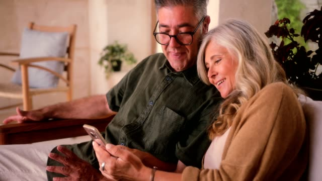 happy mature couple using smartphone and relaxing together at home - coppia anziana video stock e b–roll