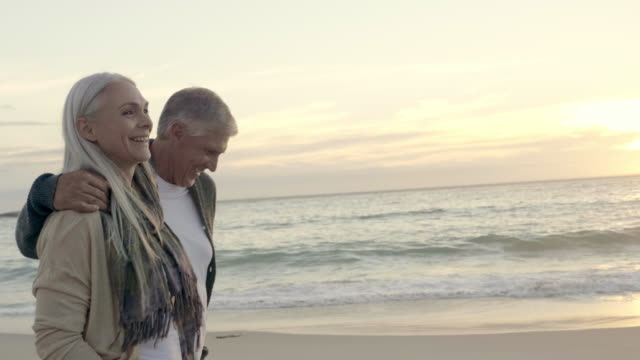 Happy mature couple walking at beach during sunset