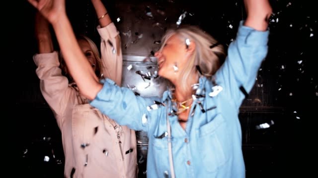 Happy mature friends celebrating and partying with confetti at night
