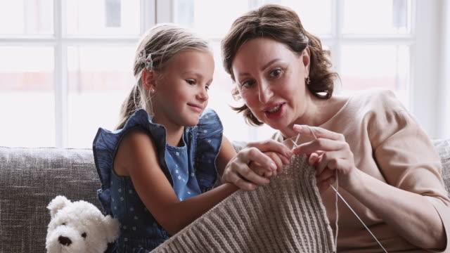Happy mature grandma teach preschool granddaughter learn knitting needles together