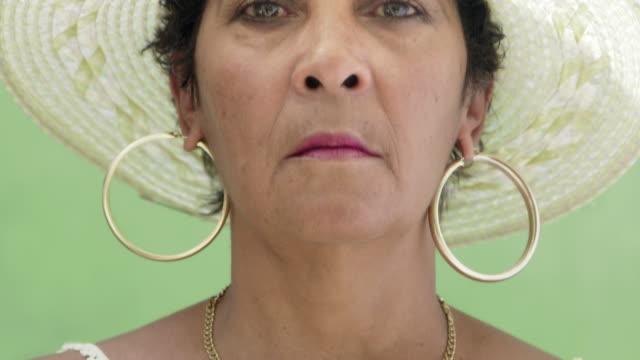 glückliche ältere hispanic frau mit hut blick in die kamera und lächelt - starren stock-videos und b-roll-filmmaterial