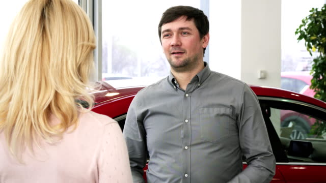 Happy mature man handing car keys to a new auto to his loving wife video