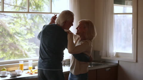 vídeos y material grabado en eventos de stock de feliz pareja mayor madura bailando riendo en la cocina - bailar