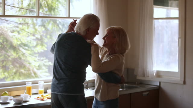 happy mature senior couple dancing laughing in the kitchen - coppia anziana video stock e b–roll