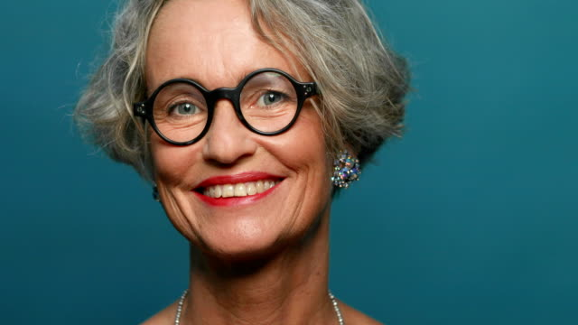 Happy mature woman against blue background Close-up portrait of happy fashionable mature woman against blue background. Smiling female is wearing geek glasses, earrings and red lipstick. She is with short gray hair. background color stock videos & royalty-free footage