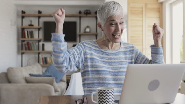 Happy mature woman celebrating while reading good new on the computer. video