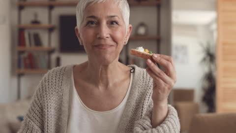donna felice matura che fa colazione a casa e mostra i pollici in su mentre guarda la macchina fotografica. - alimentazione sana video stock e b–roll