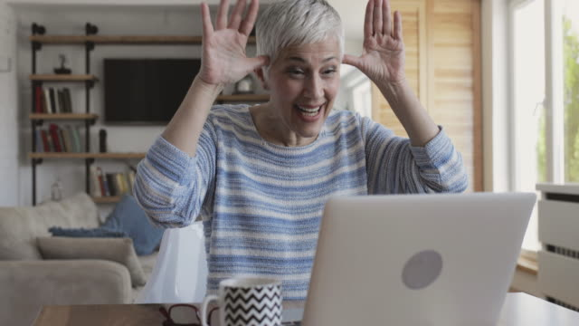 Happy mature woman having fun during video chat over laptop. video