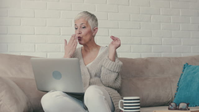 Happy mature woman sending kisses and waving while having video chat over laptop. video