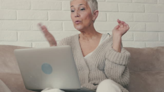 Happy mature woman sending kisses and waving while using laptop and  communicating with someone through the internet. video