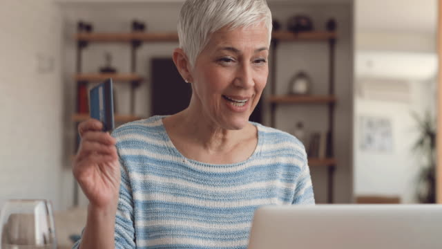 Happy mature woman shopping online with credit card and laptop at home. video