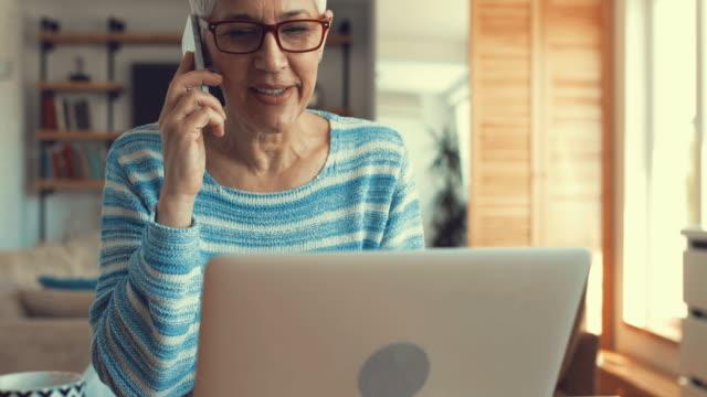 vídeos de stock, filmes e b-roll de mulher madura feliz conversando com alguém sobre telefone inteligente e usando o laptop. - no telefone