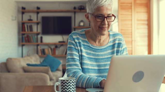 Happy mature woman typing e-mail on laptop and looking at the camera. Senior woman using laptop at home. At the end of video she is smiling and looking at the camera. adult stock videos & royalty-free footage