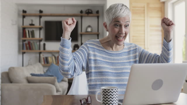Happy mature woman using laptop and celebrating good news. Senior woman surfing the net on laptop at home and celebrating with her hands raised. good news stock videos & royalty-free footage
