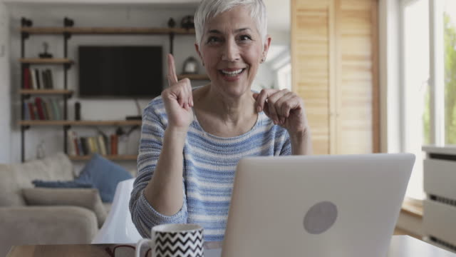 Happy mature woman using laptop at home and showing thumbs up while looking at camera. video