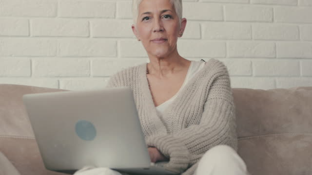 Happy mature woman using laptop on the sofa and looking at camera. video