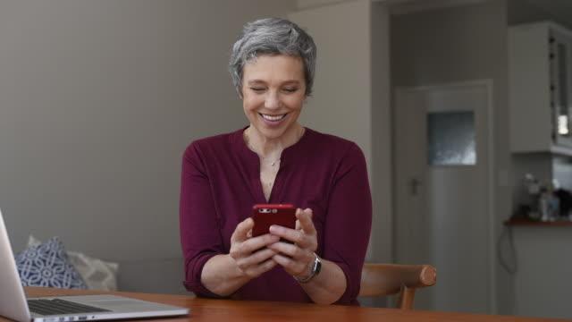 vídeos de stock e filmes b-roll de happy mature woman using smartphone at home - senior woman