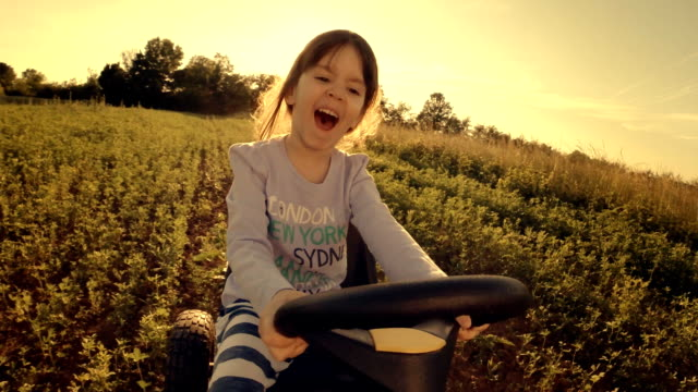 Happy Memories Of Her Young Days- A Child of Tree Drive Go-chart, Off-Road POV, User Generated Content. A Kid of Tree Playing In The Filled. Lens Flare, Slow Motion, Unusual Angle, GoPro. go cart stock videos & royalty-free footage