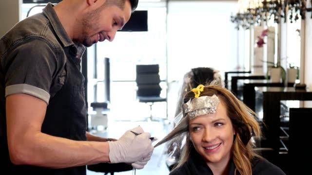 ヘアスタイリストと彼女は語って半ば大人の女性の笑顔で幸せです - 美容室のビデオ点の映像素材/bロール