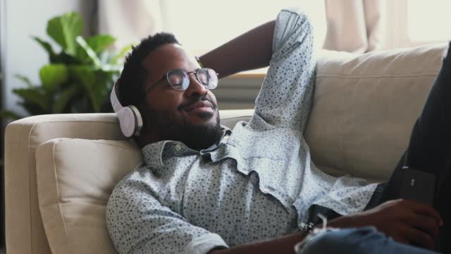Happy millennial biracial hipster guy enjoying favorite music.