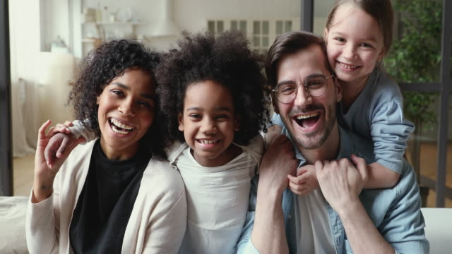happy mixed ethnicity family laughing, cuddling at home, portrait - couple portrait caucasian video stock e b–roll