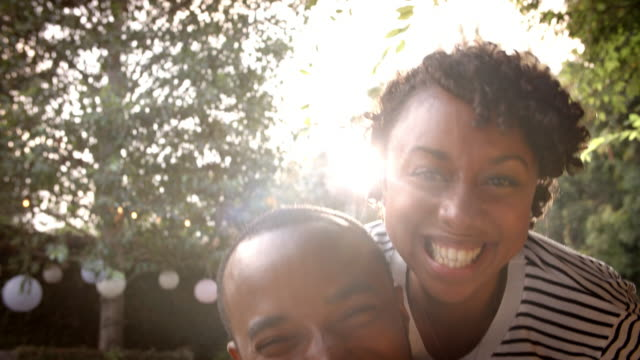 Happy mixed race couple piggybacking in garden, close up video