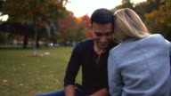 istock Happy mixed race couple sitting at picnic table in park 1220669949