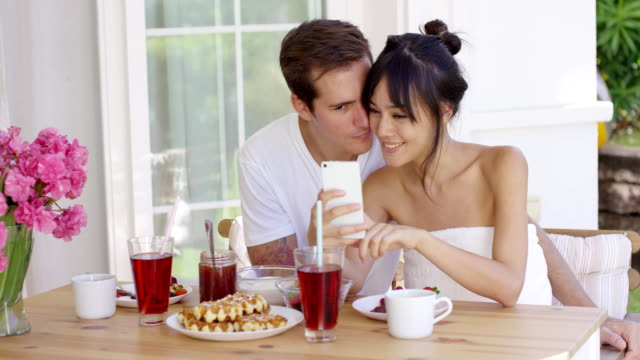 Happy mixed race couple taking selfie Happy mixed race couple sitting on terrace  having a teasty breakfast. They taking selfie photo with their mobile phone. wearing a towel stock videos & royalty-free footage