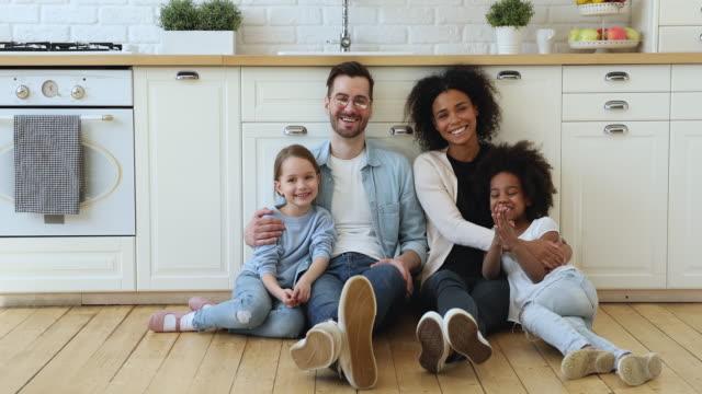glückliche gemischte rasse familie sitzt auf küchenboden zu hause - person gemischter abstammung stock-videos und b-roll-filmmaterial