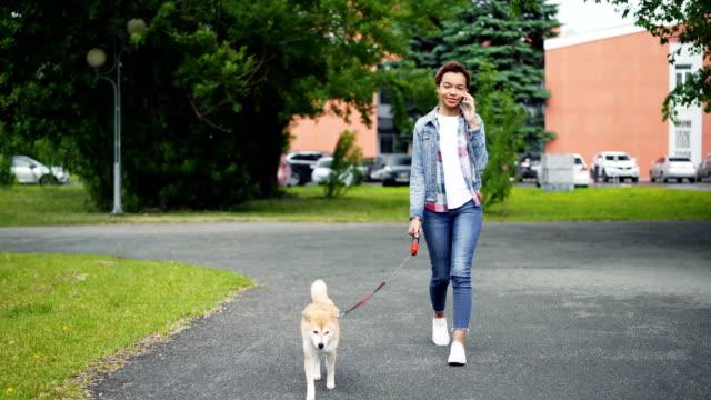 glücklich mischlinge mädchen geht in den park und telefonieren mit handy, die kommunikation mit freunden spazieren. moderne technik, tiere und kommunikationskonzept zu lieben. - hundesitter stock-videos und b-roll-filmmaterial