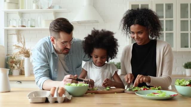 glada blandade ras föräldrar och afro-amerikansk dotter matlagning tillsammans - hälsosamt ätande bildbanksvideor och videomaterial från bakom kulisserna