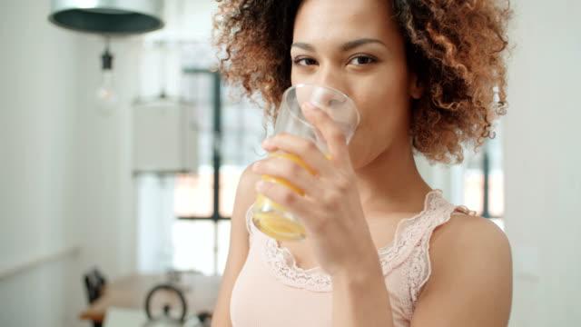 vídeos y material grabado en eventos de stock de mujer mestiza feliz celebración de jugo de naranja y mirando a cámara. - zumo